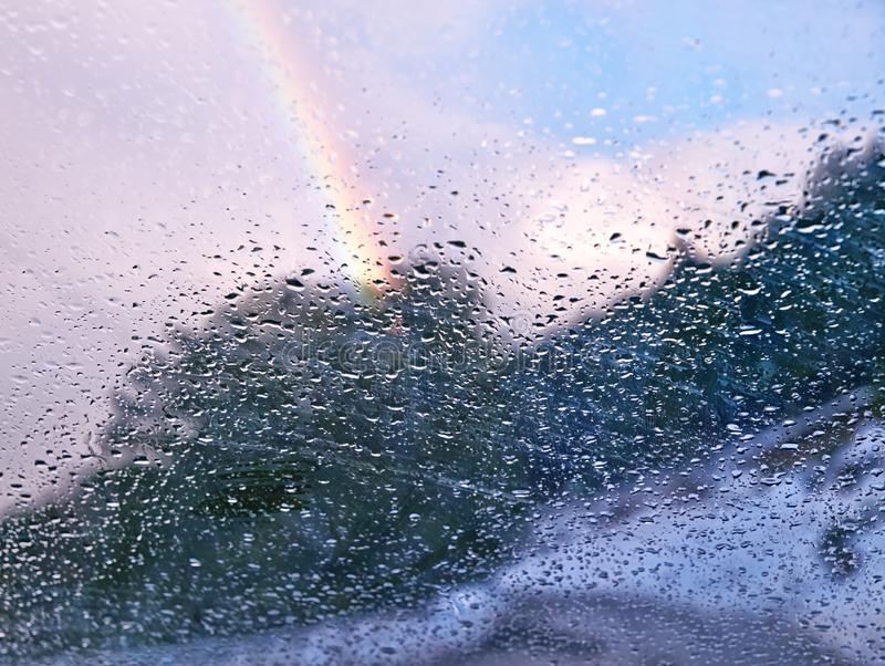 Rainbow behind car window glass with rain drops. After rain concept. Selective focus on window glass. White, closeup, bright, blur, joy, day, blue, light stock image
