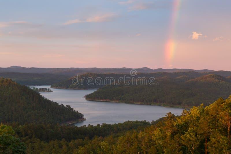 Rainbow at Broken Bow Lake. A rainbow in the sky during a beautiful sunset at Broken Bow Lake, Oklahoma royalty free stock image
