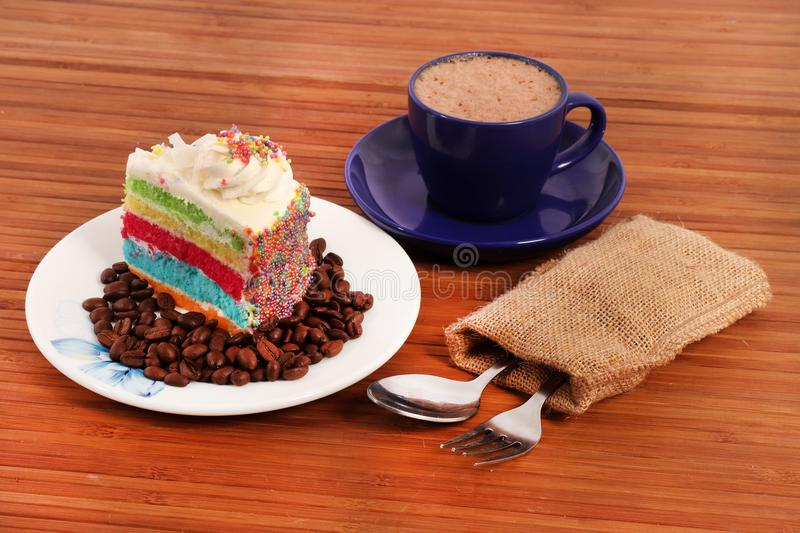 Rainbow cake slice with coffee royalty free stock images