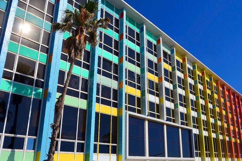 Rainbow cheerful office / residential building with windows. The facade of the house with a palm tree against blue sky in Israel. Rainbow cheerful office / stock photos