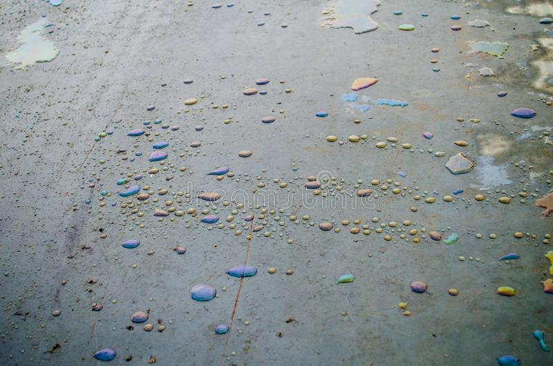 Rainbow chemical stains on the water in a puddle on road. stock photo