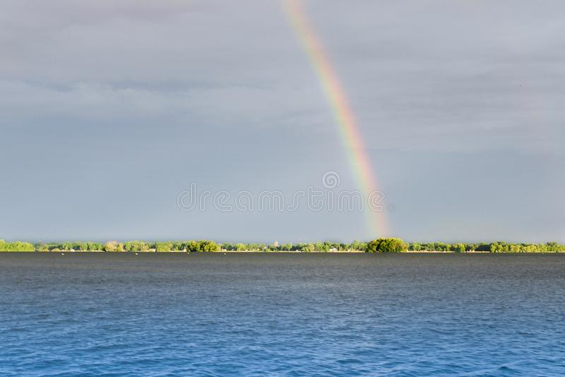 Rainbow with cloudy sky over lake stock photos