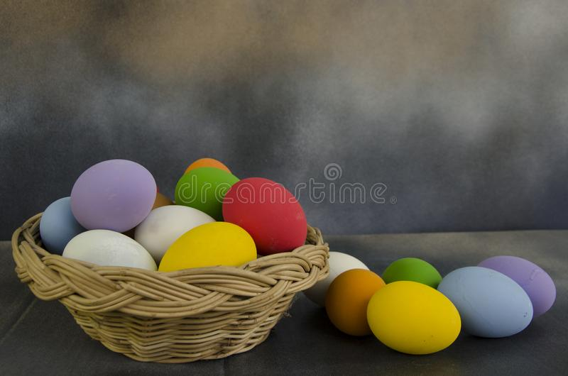 Rainbow color of egg in rattan basket and on the floor stock image