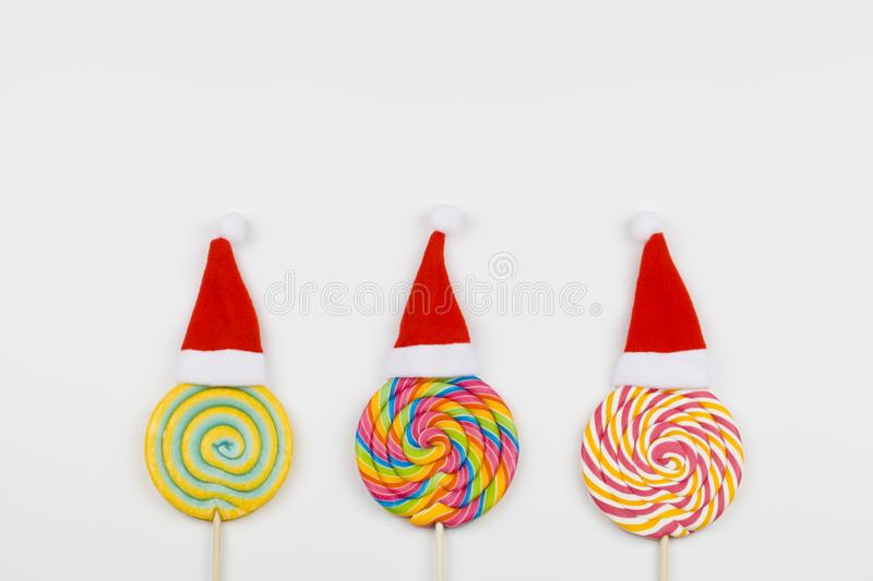 Rainbow color lollipops with santa claus hats on white background, copy space isolated on white. Christmas background stock photo