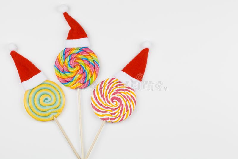 Rainbow color lollipops with santa claus hats on white background, copy space  on white. Christmas background royalty free stock photography