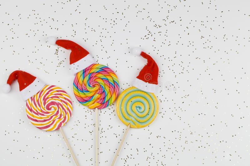 Rainbow color lollipops with santa claus hats on white background with small stars, copy space isolated on white. Christmas background stock image