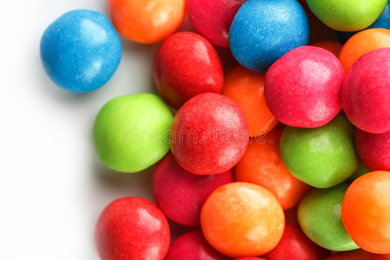 A rainbow of color from multicolored candies close-up, multi-colored glaze dragee on a white background stock photo