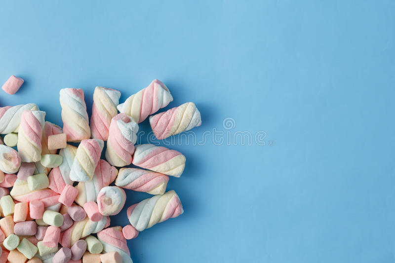 Rainbow color of spiral marshmallows on blue background stock photos