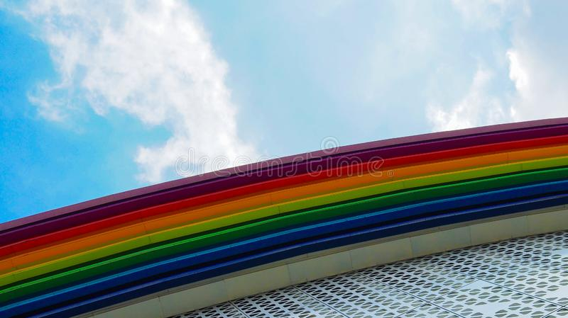 Rainbow colored building. And sky with clouds royalty free stock image