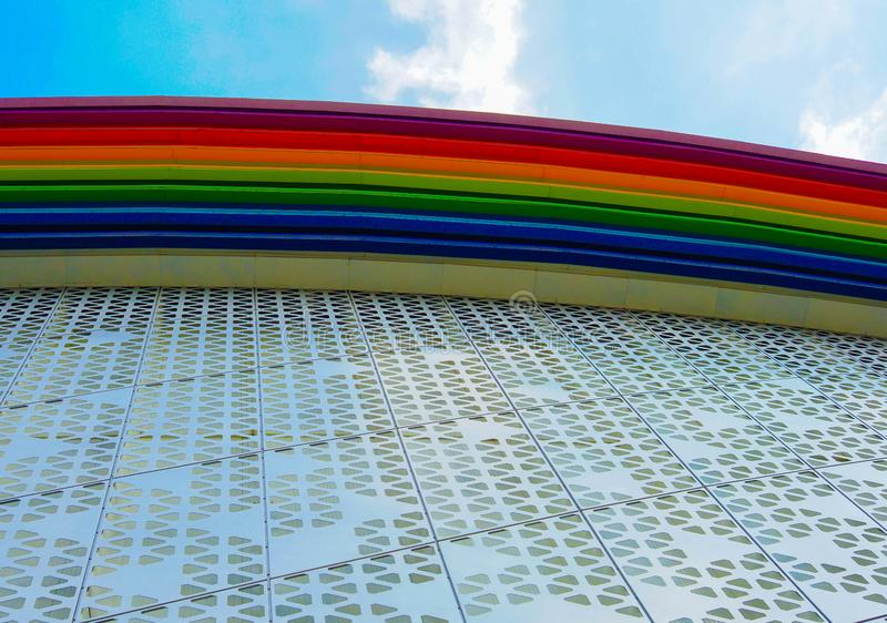 Rainbow colored building. And sky with clouds stock image