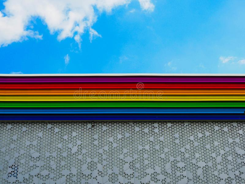 Rainbow colored building. And sky with clouds stock images