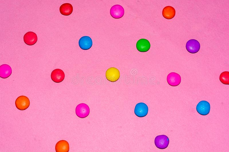 Chocolate coated candies on pink background. Rainbow colored chocolate coated candies on pink background and flat lay stock images