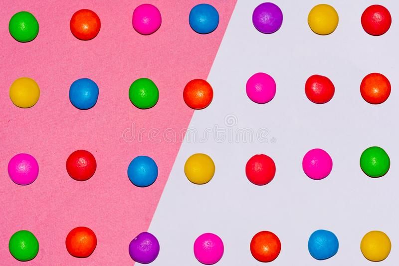 Chocolate coated candies on pink and white background. Rainbow colored chocolate coated candies on pink and white background stock photography