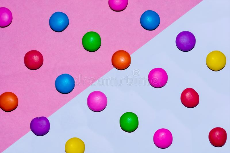 Chocolate coated candies on pink and white background. Rainbow colored chocolate coated candies on pink and white background stock photos