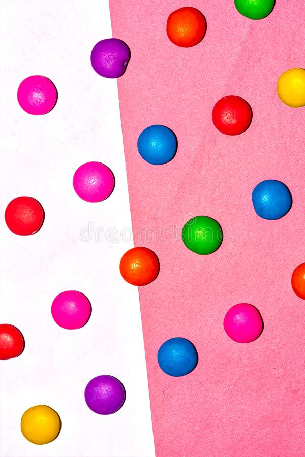 Chocolate coated candies on pink and white background. Rainbow colored chocolate coated candies on pink and white background stock photo
