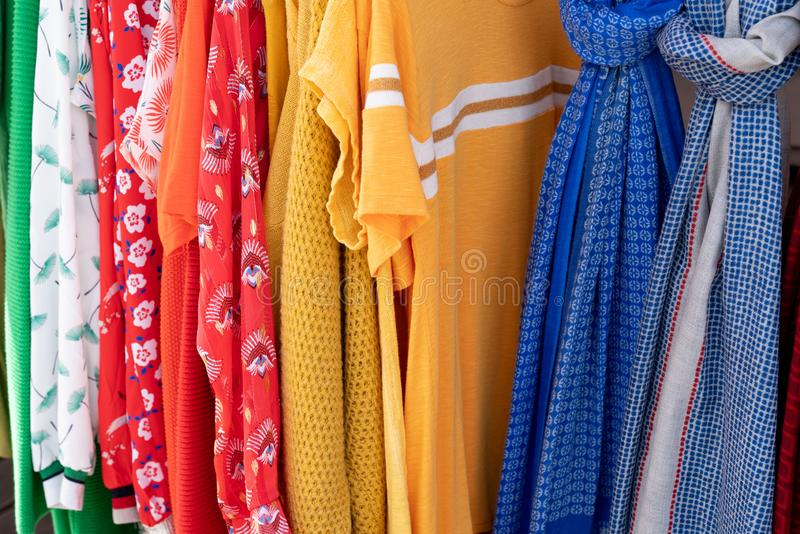 Rainbow colored clothes on hangers in a retail shop in Fashion and shopping concept stock photos