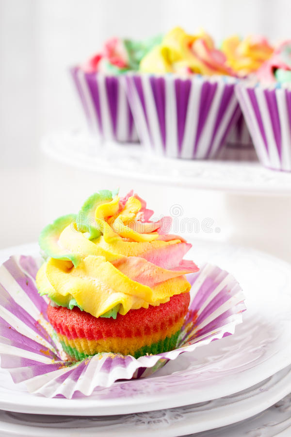Rainbow colored muffins stock image