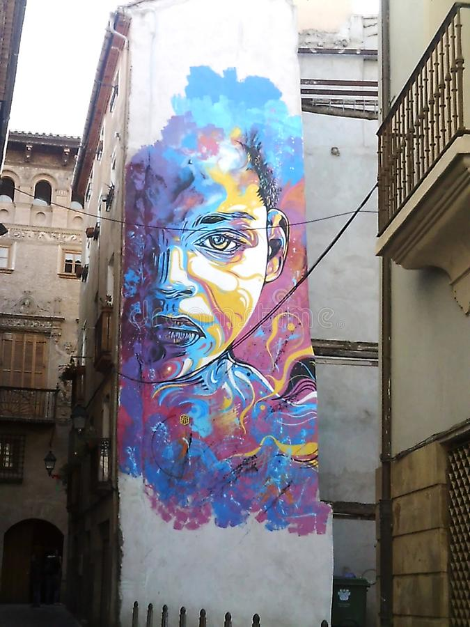 Rainbow colored mural at Tudela Spain. Rainbow colored mural of a human face in a street at Tudela Spain stock photo
