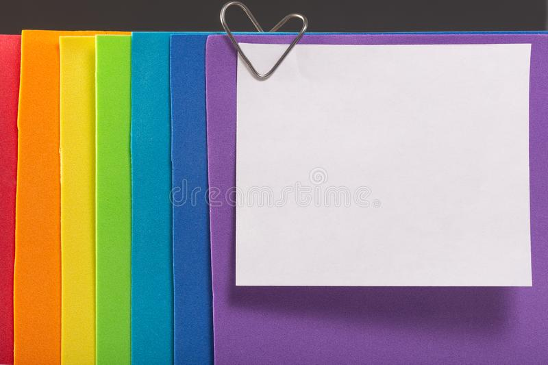A rainbow colored note paper with a heart clip. The concept of love and Valentine`s Day for same-sex couples royalty free stock photography
