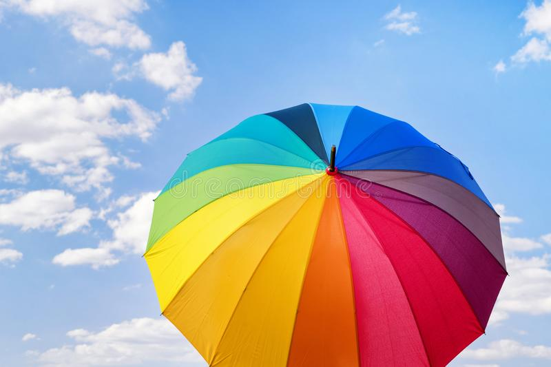 Rainbow colored umbrella against blue cloudy sky royalty free stock photo