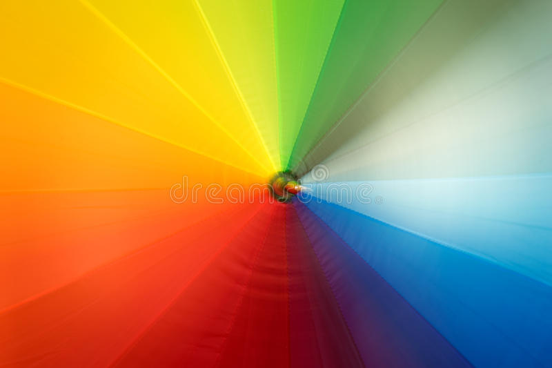 Rainbow colored umbrella in motion. Texture of rainbow colored umbrella in motion stock images