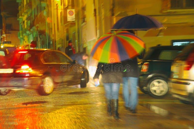 Rainbow colored umbrella under rain. A person with rainbow colored umbrella walking in the rain, motion blur stock image