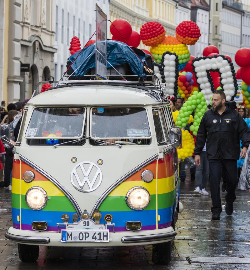 Rainbow colored VW bus and people attending the Gay Pride parade also known as Christopher Street Day CSD in Munich, Germany. 2019: Rainbow colored VW bus and stock photo