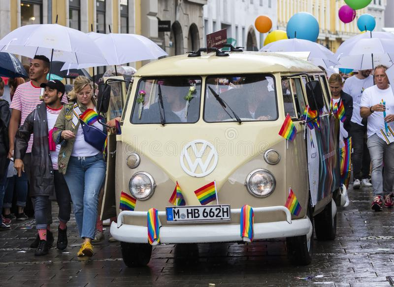 Rainbow colored VW bus and people attending the Gay Pride parade also known as Christopher Street Day CSD in Munich, Germany. 2019: Rainbow colored VW bus and royalty free stock image