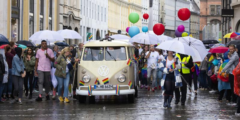 Rainbow colored VW bus and people attending the Gay Pride parade also known as Christopher Street Day CSD in Munich, Germany. 2019: Rainbow colored VW bus and royalty free stock photography