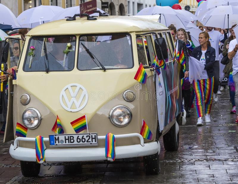 Rainbow colored VW bus and people attending the Gay Pride parade also known as Christopher Street Day CSD in Munich, Germany. 2019: Rainbow colored VW bus and stock photography