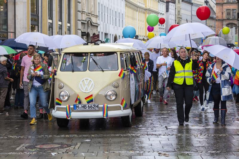 Rainbow colored VW bus and people attending the Gay Pride parade also known as Christopher Street Day CSD in Munich, Germany. 2019: Rainbow colored VW bus and royalty free stock images
