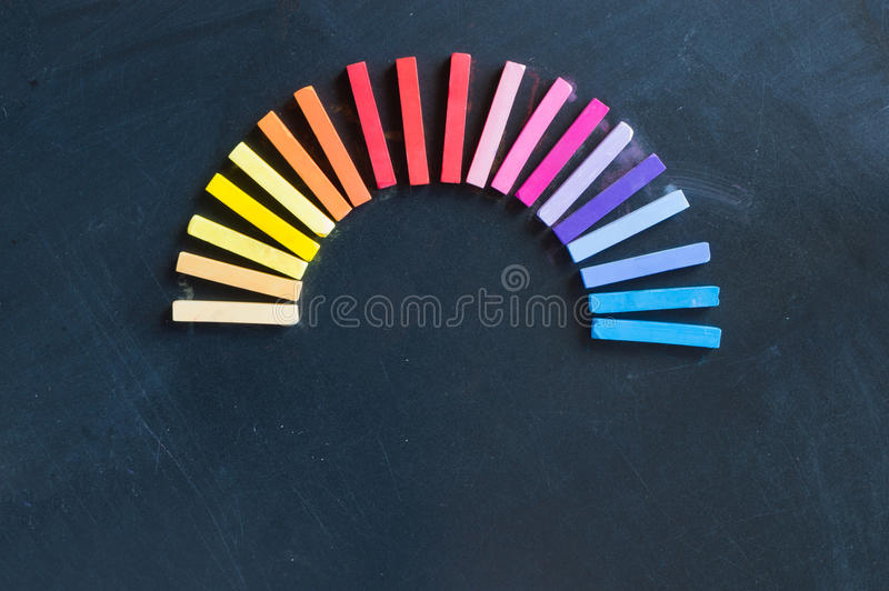 Rainbow of colorful chalks lined up rounded on circle. Rainbow of colorful chalks and soft pastels lined up rounded on circle on blackboard background stock photo