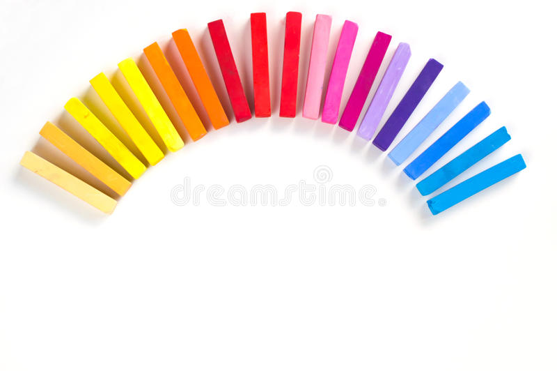 Rainbow of colorful chalks and pastels lined up rounded on circle. On white background royalty free stock photography