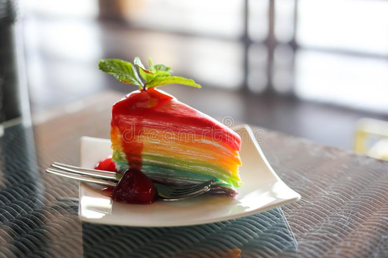 Rainbow Colorful crepe cake with strawberry sauce with cold coffee royalty free stock image