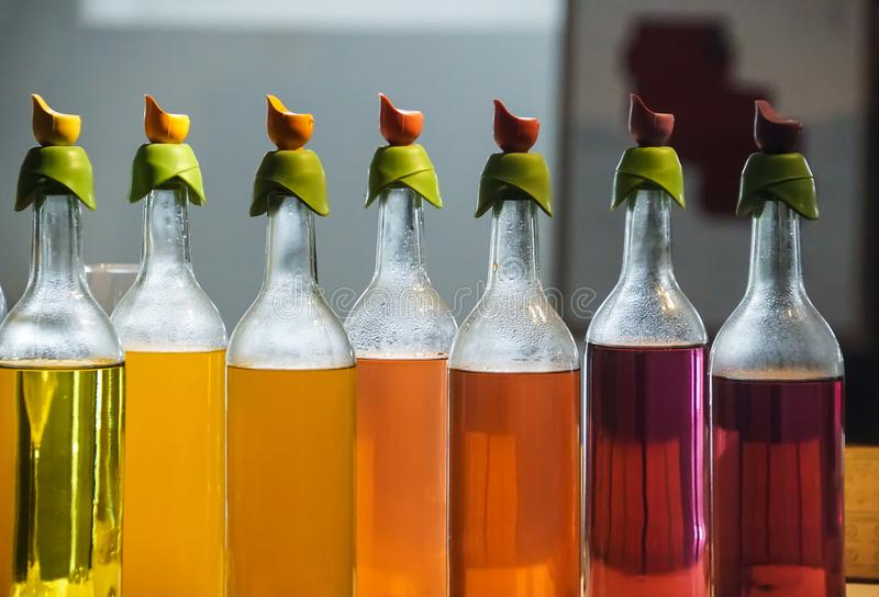 Rainbow colorful drink in bottles, yellow, orange, red, pink, purple royalty free stock photo