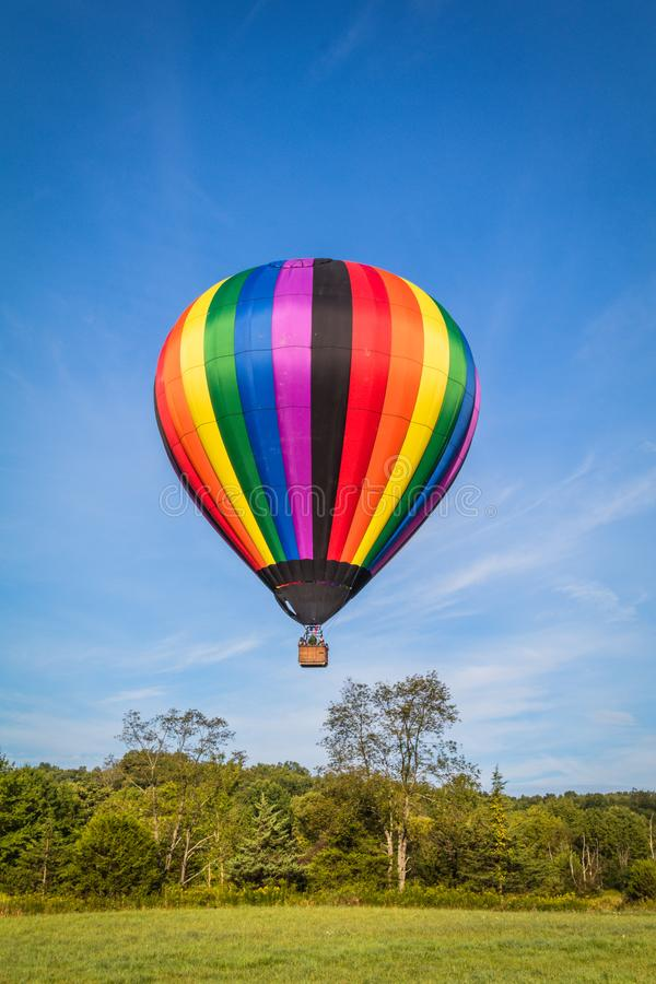 Rainbow colorful hot-air balloon floats on a summer morning with bright blue sky royalty free stock photo