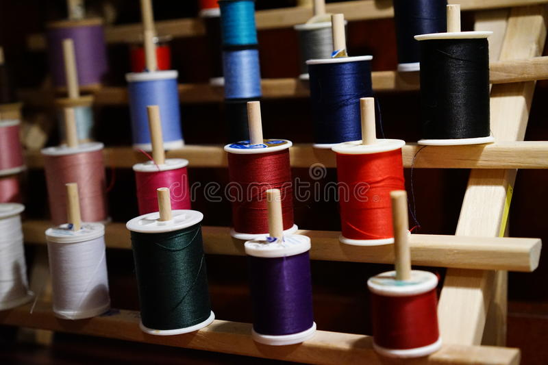 A rainbow of colorful thread. Spools of vivid thread colors perched on wooden rack are ready for use royalty free stock photo