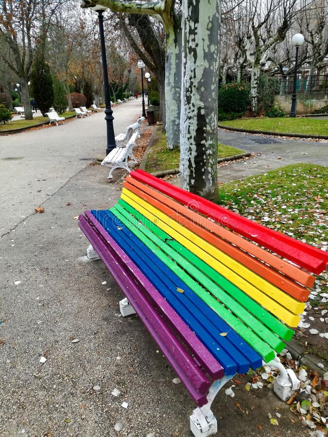 Rainbow colors wooden bench. Wooden bench painted in rainbow colors in a quiet park stock photos