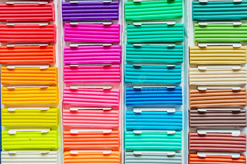 Rainbow colors of modeling clay. Multicolored plasticine bars ina box, background texture stock images