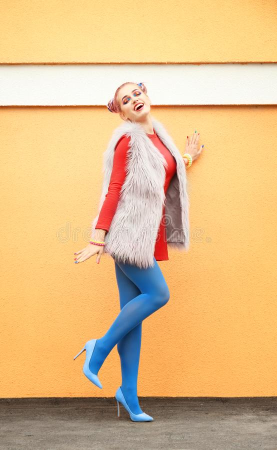 Rainbow colors for trendy look. Young stylish woman near color wall, outdoors royalty free stock photos