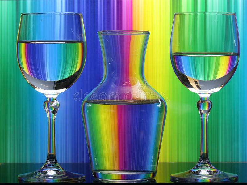 Two wine glasses and a jug of fresh clean water on a coloured background stock photo