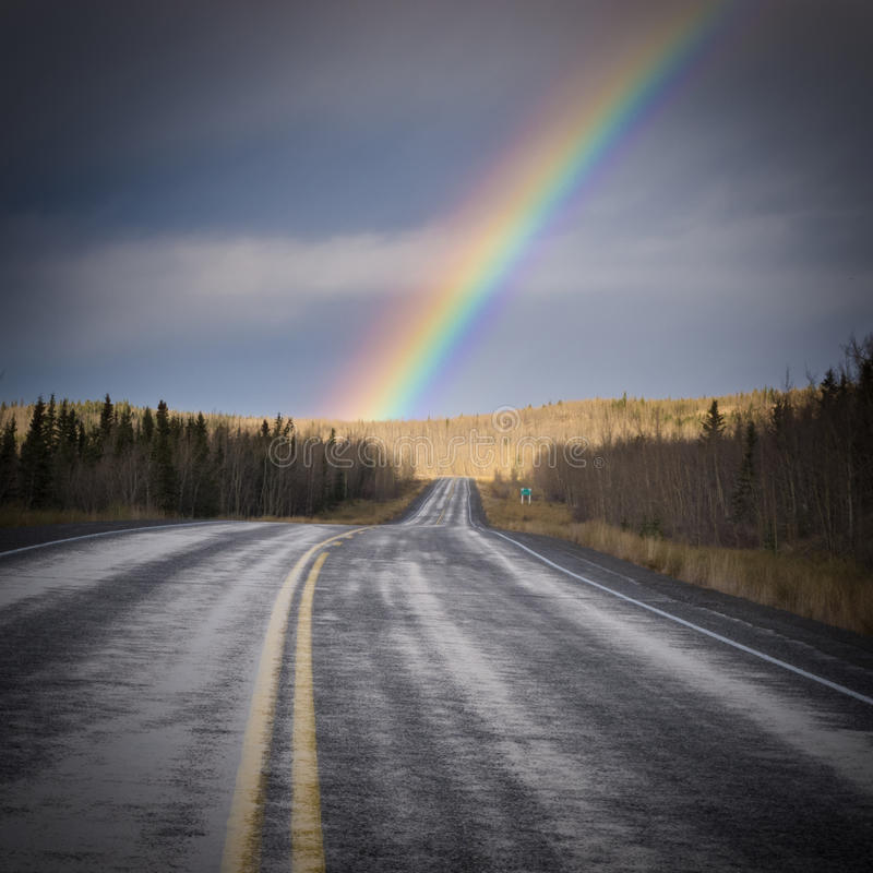 Rainbow country road dark Yukon nature landscape. Wet asphalt road leading to colourful rainbow over late fall forested landscape after rain in Yukon Territory royalty free stock photo