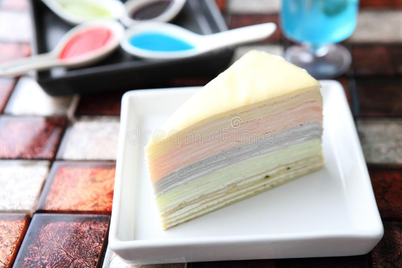 Rainbow Crepe cake. On a plate royalty free stock photo