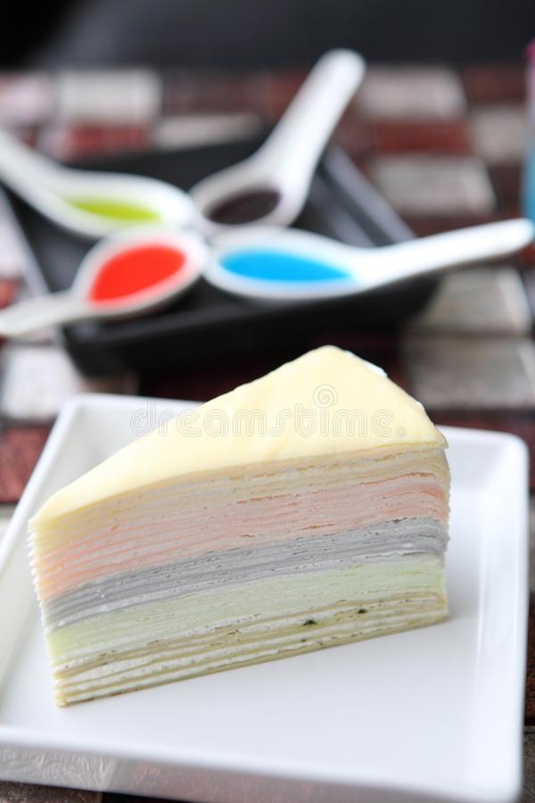 Rainbow Crepe cake. On a plate royalty free stock photos