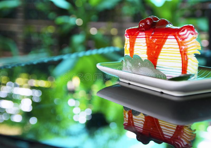Sweet rainbow crape cake with strawberry sauce topping on plate on the table and shadow green tree background, snack menu at cafe. Rainbow crape cake and white stock photos