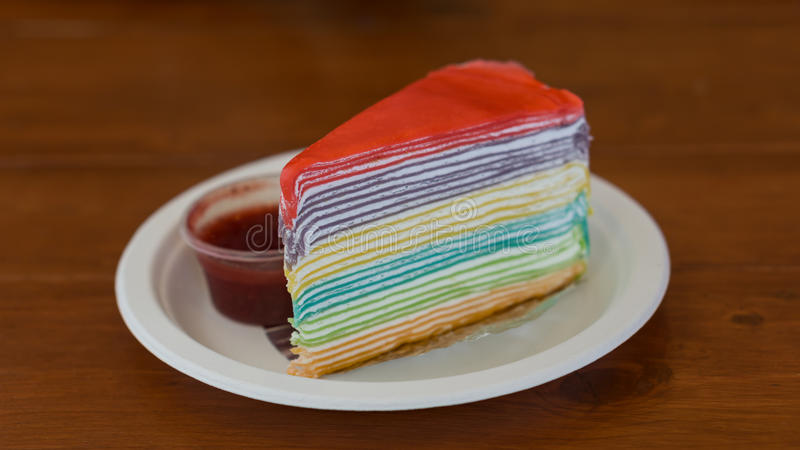 Rainbow crape cake. On white plate and on wood tableSelective Focus royalty free stock photography