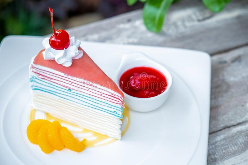 Rainbow crepe cake and a cherry with strawberry sauce stock photo