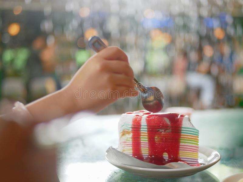 Rainbow crepe cake with strawberry sauce, with a baby`s hand about to scoop it, on a ceramic plate served on a table royalty free stock photo