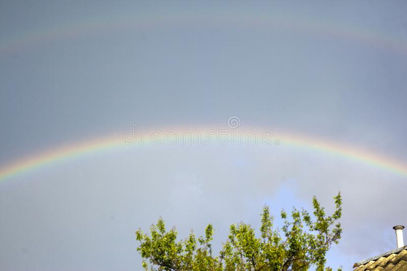 Rainbow in the dark sky after the rain. Landscape royalty free stock images