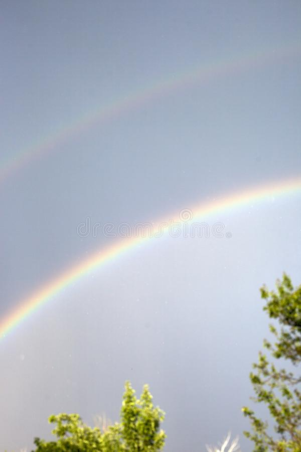 Rainbow in the dark sky after the rain. Landscape royalty free stock photos